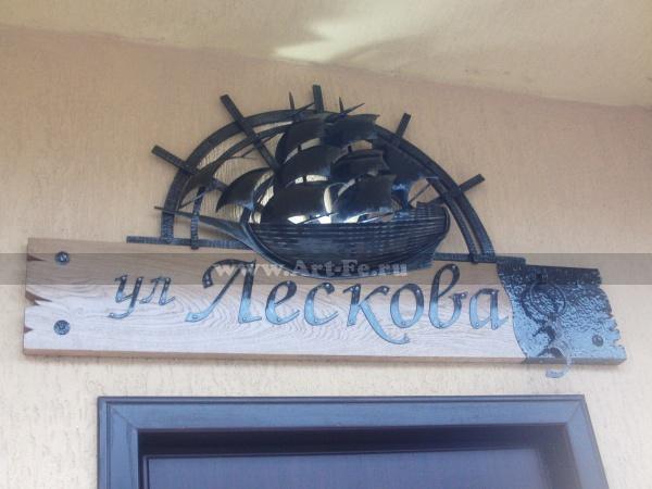 Название улицы табличка с номером дома, ковка и дерево